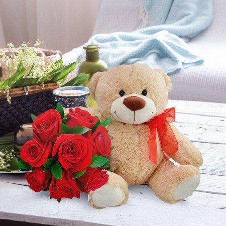 Urso de pelúcia com buquê de rosas vermelhas