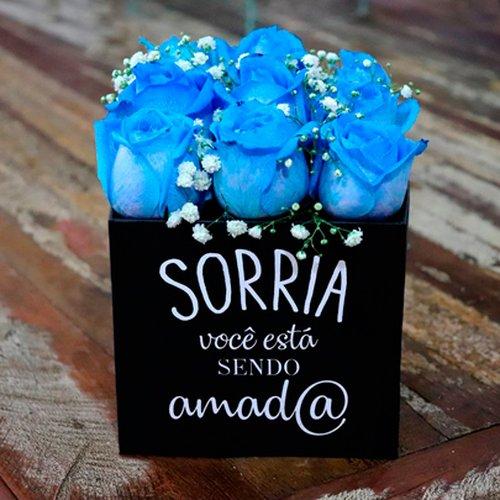 """Rosas azuis no box """"Sorria você está sendo amad@"""""""